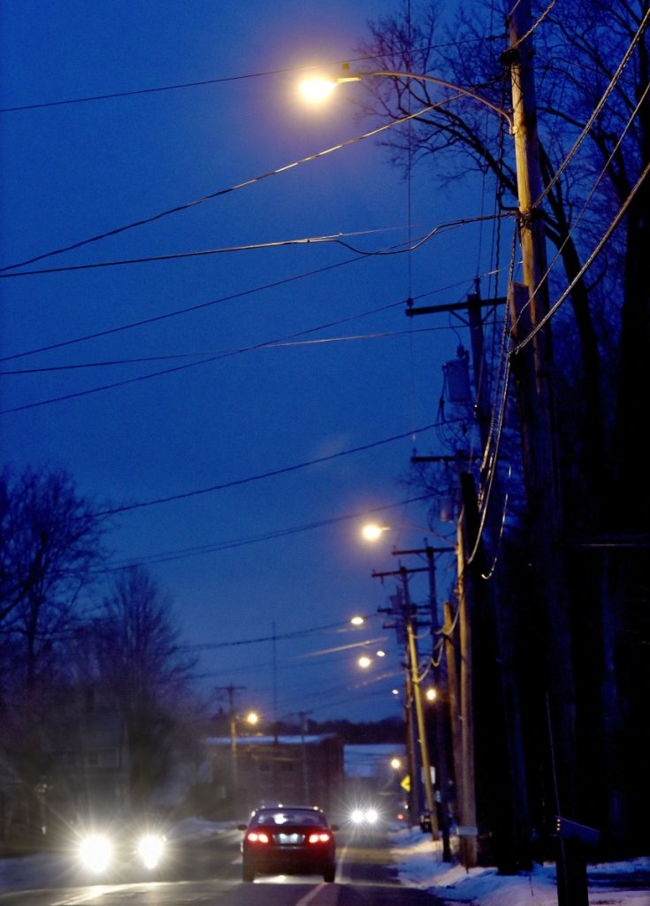 Street lights illuminate Main Street in Vassalboro in late November as traffic passes through town. The town is planning to upgrade lights to LED through Central Maine Power.
