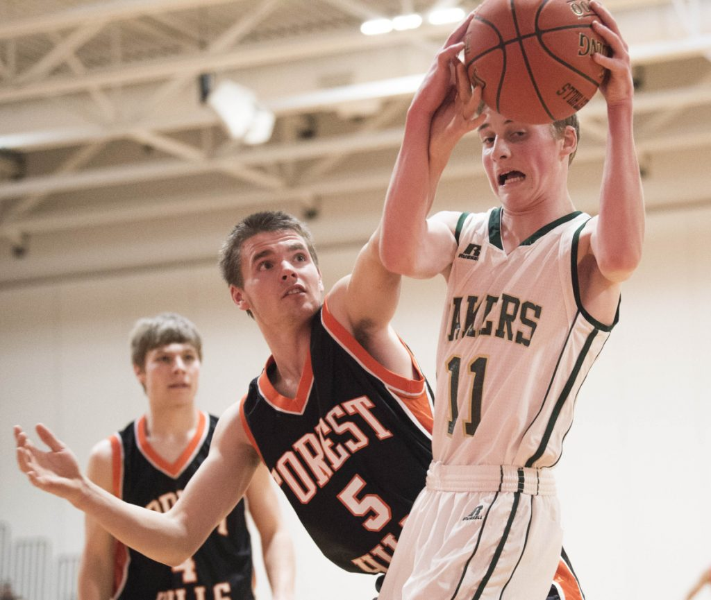 Rangeley's Nolan Boone (11) battles for the rebound with Forest Hills' Brandon Gilboe (5) on Saturday at Cony High School in Augusta.