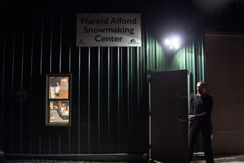 WATERVILLE, ME - DECEMBER 30, 2018   Dave MacLeay, president of the board of the Friends of Quarry Road, exits the Harold Aflond Snowmaking Center at Quarry Road late Saturday night after a failed attempt to make snow in Waterville on Sunday, Dec. 30, 2018. Donovan talks on the phone as seen through the window with snowmaking volunteer crews to stay home for the night. The compressor on lease that pumps the water to the snow guns wouldn't start and is on hold for operation until  Sunday morning which means snowmaing operations will have to be rescheduled, weather conditions permitting.(Morning Sentinel photo by Michael G. Seamans/Staff Photographer)