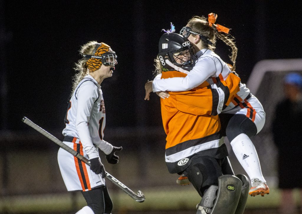 Gardiner's Jillian Bisson, right, jumps into the arms of goalie Lindsey Bell after they defeated Winslow in the Class B North championship game this fall in Waterville.