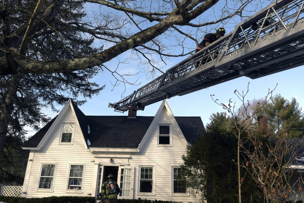 Firefighters extinguish a blaze Monday morning on Neck Road in West Gardiner. Firefighters returned to the farmhouse to discover a fire on the second floor after battling a chimney fire at the residence the night before.