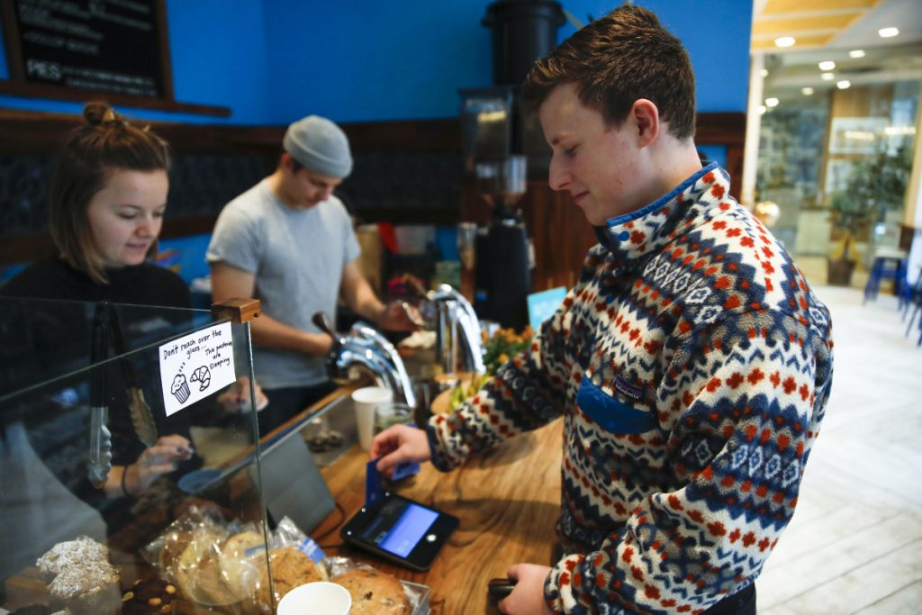 Eli Gitelman swipes his card to pay his bill and add a tip at a Dollop coffee shop in Chicago. More people who pay with a card are encountering a tip screen prompting them to add a gratuity for a service they may not have considered tipping for before, creating a quandary about the tip in the middle of a transaction.