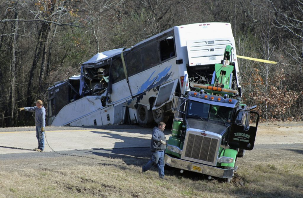 Employees from a wrecker service work to remove a charter bus from a roadside ditch Monday after it crashed alongside Interstate 30 near Benton, Ark. The bus was carrying a youth football team from Tennessee when it rolled off an interstate off-ramp and overturned before sunrise Monday. The elementary-school age football team from Orange Mound Youth Association in southeast Memphis had played in a tournament in Dallas over the weekend.