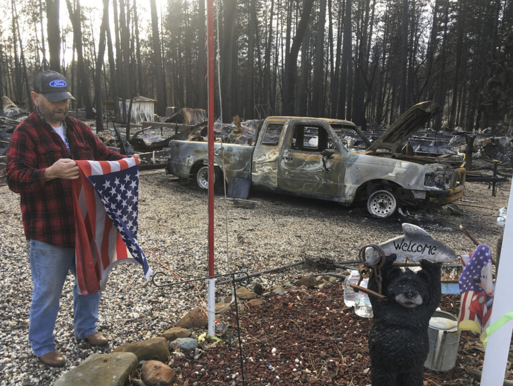 Jerry McLean folds the flag that was flying outside the remains of his home Wednesday, in Paradise, Calif. Some residents of the town devastated by wildfire nearly a month ago were finally allowed to return home.