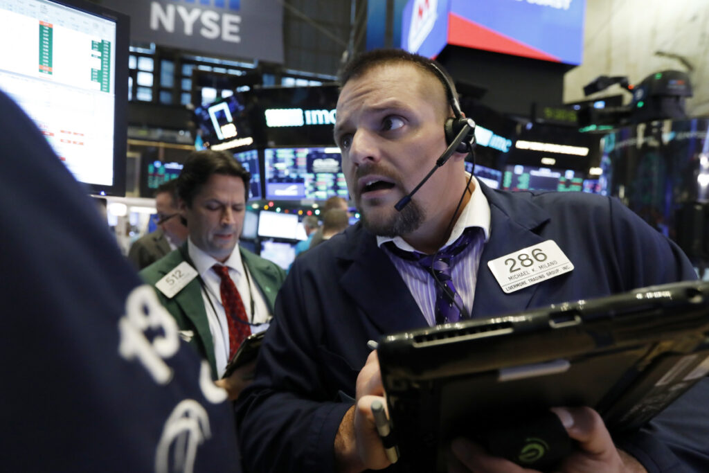 Trader Michael Milano, right, works on the floor of the New York Stock Exchange on Monday.