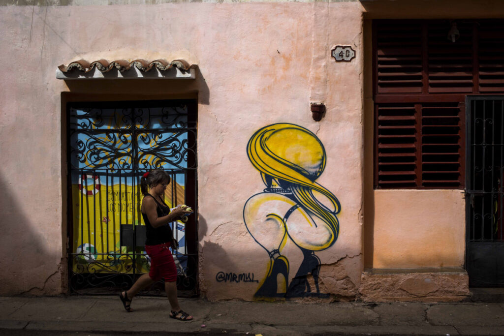 A woman passes by a closed art store decorated by a mural in Havana, Cuba, on Dec. 5. Associated Press/Desmond Boylan