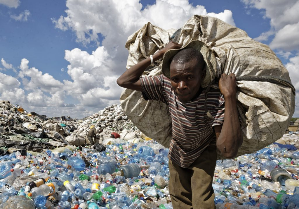 A man walks on a mountain of plastic bottles as he carries a sack of them to be sold for recycling after weighing them at the dump in the Dandora slum of Nairobi, Kenya.