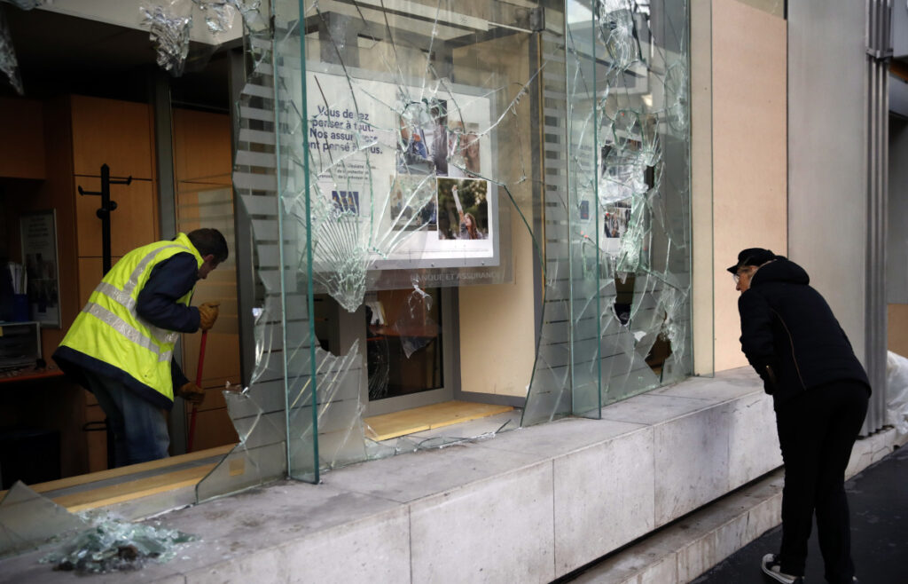 A worker clears debris from a Paris bank on Sunday as the city cleaned up from protests.