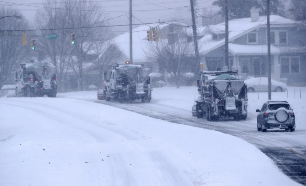 A driver in a small car follows three snow plows down a major road in Greensboro, N.C., on Sunday. A massive storm brought snow, sleet, and freezing rain across a wide swath of the South.