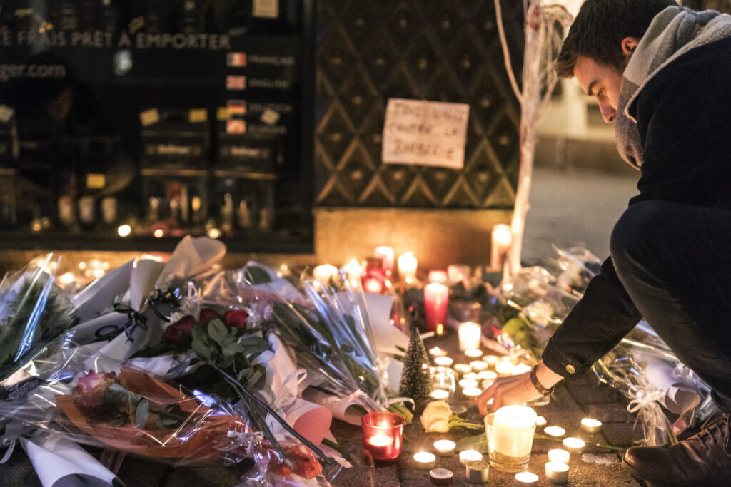 A man lights a candle Wednesday as he pays respects to the victims of an attack the night before that killed two and injured 13 in Strasbourg, eastern France. The suspected gunman had been flagged for extremism and was on a watch list.
