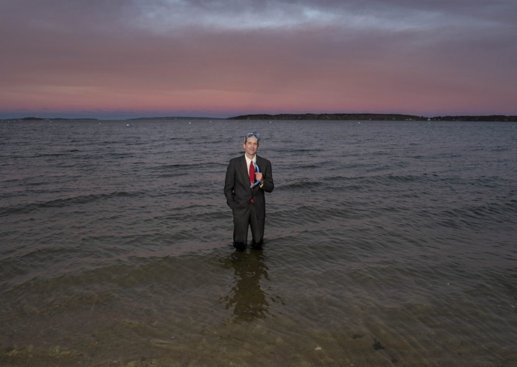 Wearing a business suit, swim goggles and holding a snorkel, Jason Wentworth stands in the water of Casco Bay off East End Beach recently. In the video on his GoFundMe page, Wentworth, who aspires to stand-up comedy focusing on climate change, swims out of the bay and walks up onto East End Beach in this get-up.