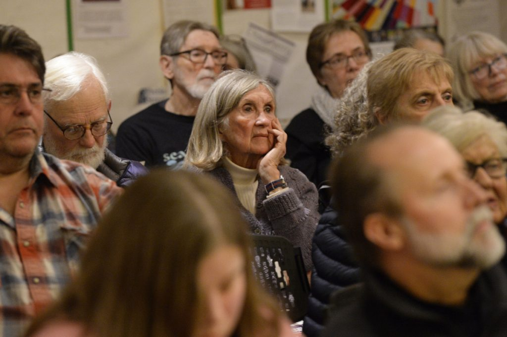 Mere Roberts of Portland, center, listens intently during the Vigil for All Victims of Gun Violence, held Friday evening at the First Parish Church in Portland.