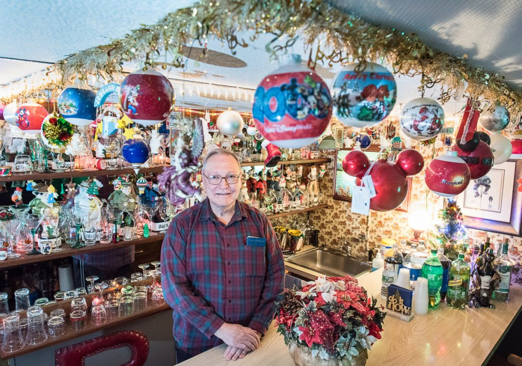 Standing behind a bar ready for a party, Roland Bergeron of Auburn has decorated the inside of his historic family homestead with thousands of Christmas decorations every year since he was a boy.