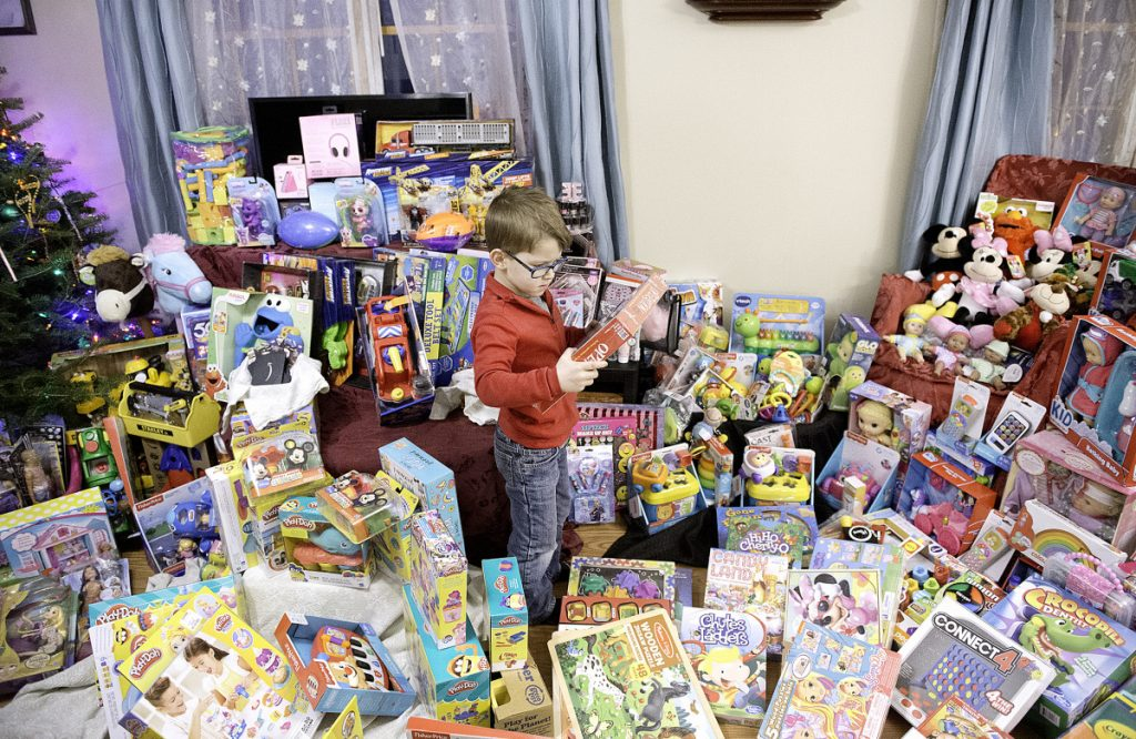 """RJ Bourgeois, 6, looks over toys for children at The Barbara Bush Children's Hospital. """"We always try to make Christmas all about family and friends,"""" his mother said. """"It's not all about presents. It's all about giving."""""""