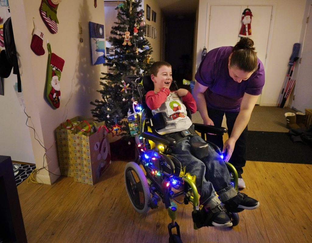 Megan Bouchard turns on lights that decorate her son Trey's wheelchair in their Freeport apartment. Bouchard is a single mother raising Trey, who has cerebral palsy and hydrocephalus, while working as a certified nursing assistant.