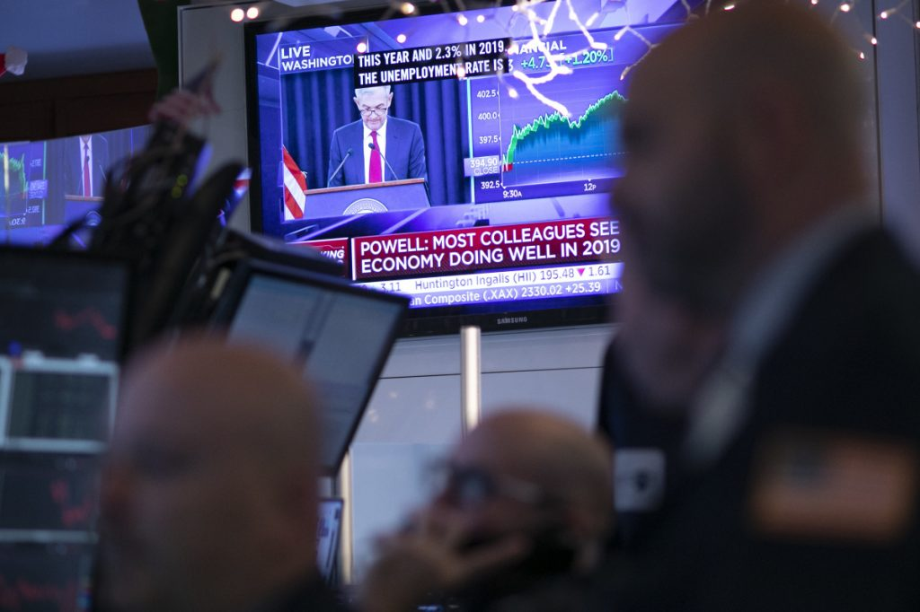 Traders at the New York Stock Exchange listen as Federal Reserve Chair Jerome Powell is seen on a video screen giving a news conference from Washington after the Fed announced a rate increase on Wednesday.