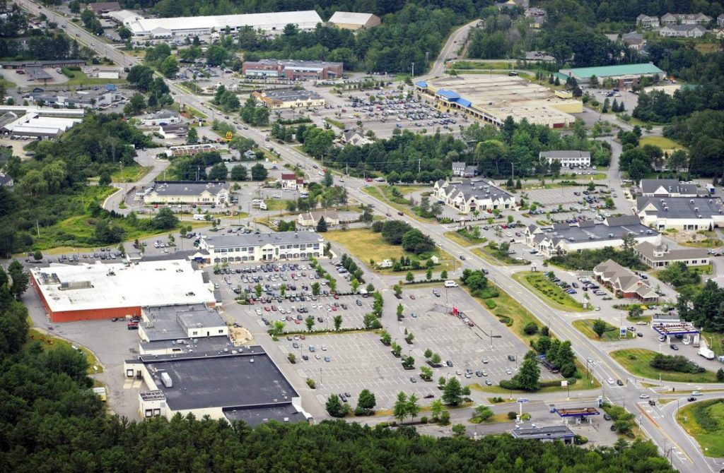 "A 2012 aerial view shows the Falmouth Shopping Center in the foreground on the left side of Route 1, looking toward Portland. ""It is our understanding,"" said Town Council Chairman Caleb Hemphill, ""that the alternative plan is not at all the preferred development option, and that the developer is still looking to build out the original plan."""