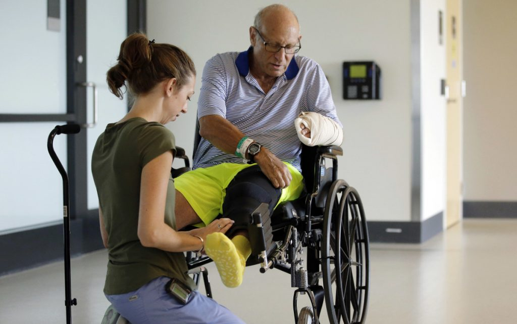 FILE - in this Aug. 28, 2018 file photo, At left,  physical therapist Caitlin Geary, right, assists William Lytton, of Scarsdale, N.Y., at Spaulding Rehabilitation Hospital in Boston. Lytton suffered deep puncture wounds to his leg and torso after being attacked by a shark on Aug. 15, while swimming off a beach in Truro, Mass. Before beaches reopen in 2019, Cape Cod is trying to determine ways to respond to the Truro attack, and to a Sept. 15 shark attack in Wellfleet, Mass., where a 26-year-old man was badly injured and later died at a hospital. It was the state's first shark attack fatality in more than 80 years. (AP Photo/Steven Senne, File)