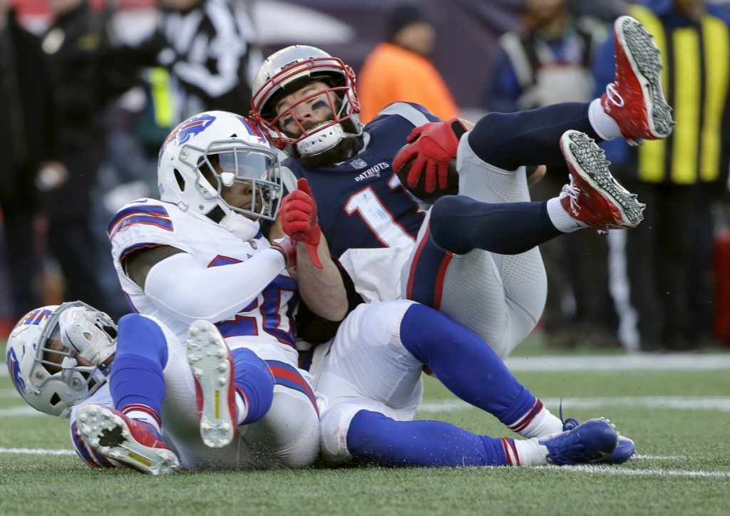 New England Patriots wide receiver Julian Edelman, right, rolls over Buffalo Bills defenders including Rafael Bush on the way to a touchdown after catching a pass during the second half of the Patriots' 24-12 win on Sunday in in Foxborough, Mass.