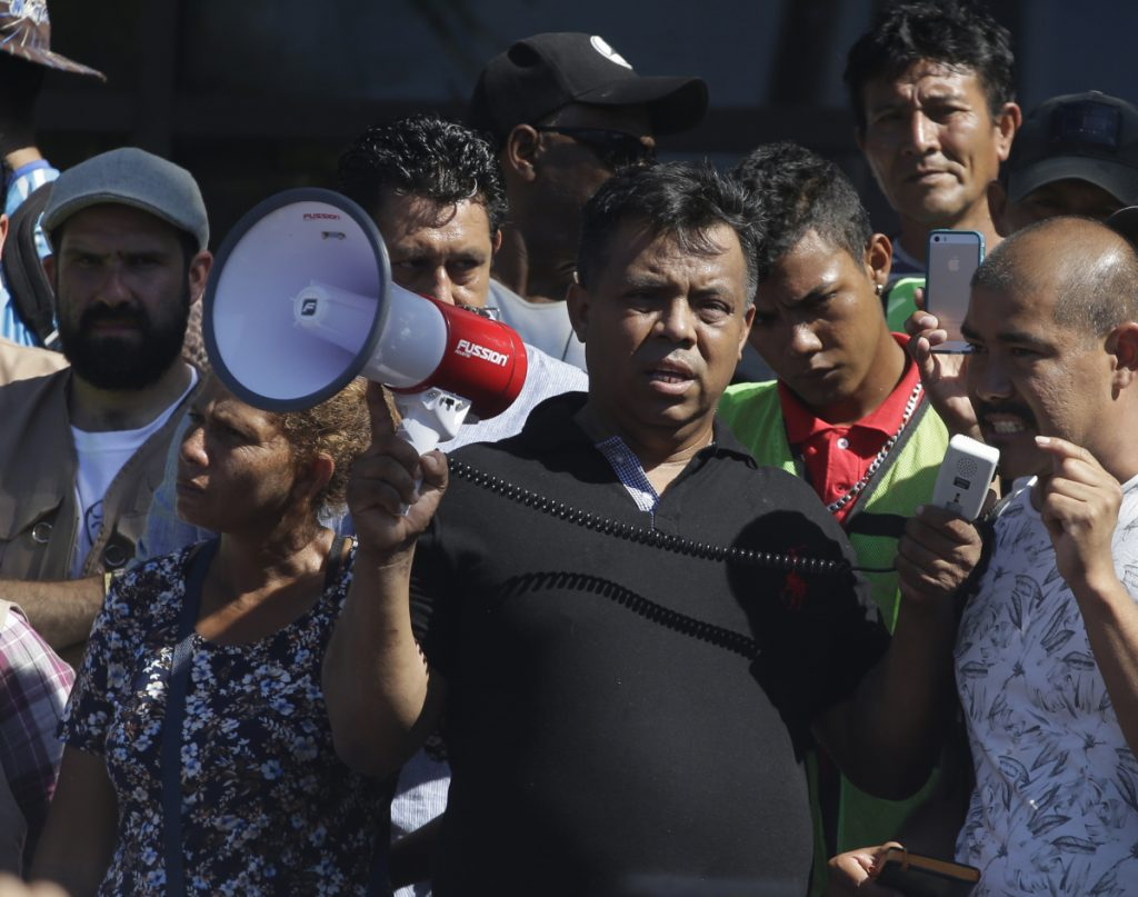 Migrant activist Irineo Mujica, center, of the group Pueblo Sin Fronteras holds a megaphone as a Central American migrant speaks to reporters during a news conference in Tapachula, Mexico, in October.