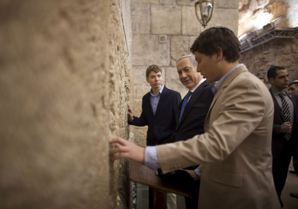 Israeli Prime Minister Benjamin Netanyahu, center, prays with his sons Yair Netanyahu, left, and Avner Netanyahu at the Western Wall in Jerusalem's old city.  Netanyahu's ruling coalition has disbanded and called an election for April 9.