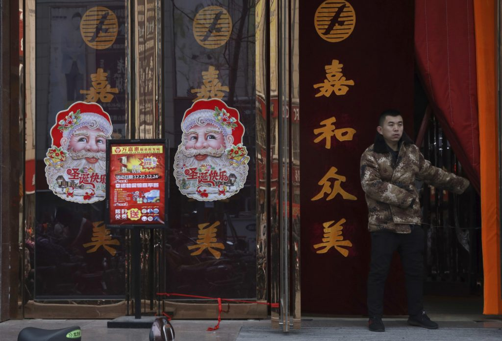 "A worker guards the entrance of a shop in Zhangjiakou in northern China's Hebei province on Saturday. The squeeze on Christmas shows how efforts to ""normalize"" thinking bleed into the everyday lives of many Chinese."