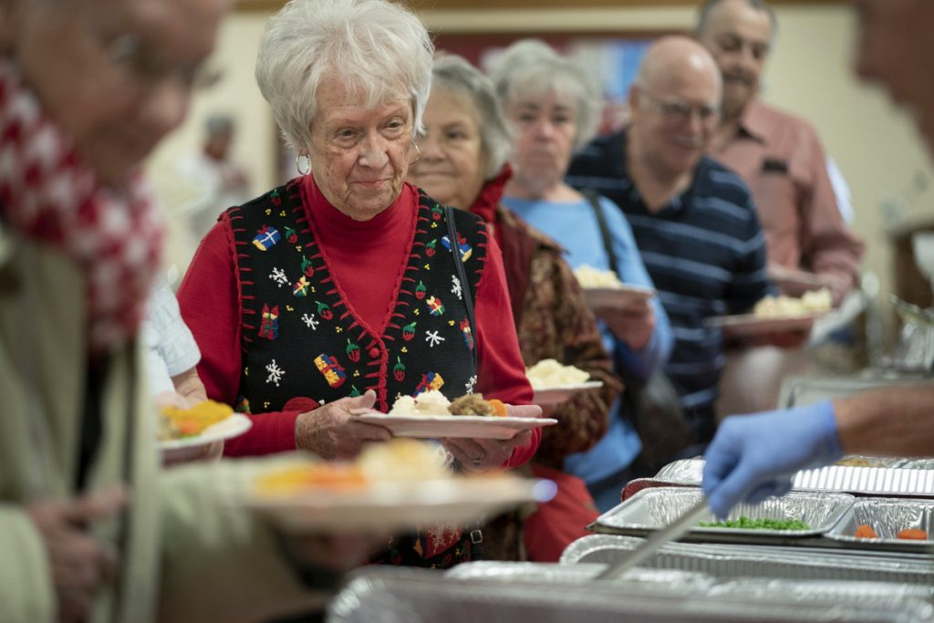 """Donna Ames, 83, of Portland waits in the serving line at a Christmas day meal at Westbrook-Warren Congregational Church in Westbrook on Tuesday. """"It's just great,"""" she said. """"They do a great job and the people here are just wonderful."""" She was dining before her night shift at Spring Harbor Hospital."""