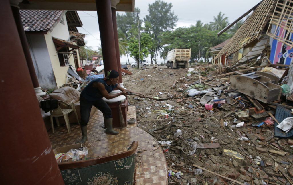 A man cleans the debris from a house at a tsunami-hit area in Carita, Indonesia, Thursday, Dec. 27, 2018. Indonesia has widened the no-go zone around an island volcano that triggered a tsunami on the weekend, killing hundreds of people in Sumatra and Java.