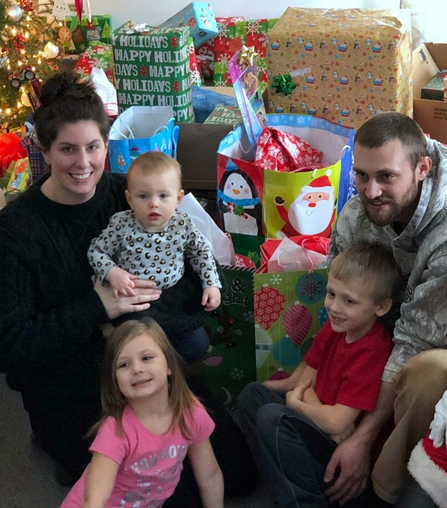 Chelsea Austin and Justin Jackson of Carthage, and their children, Quinn, Eloise and Brock, sit among gifts donated by people in the area after the family's home burned Dec. 21, in top photo.