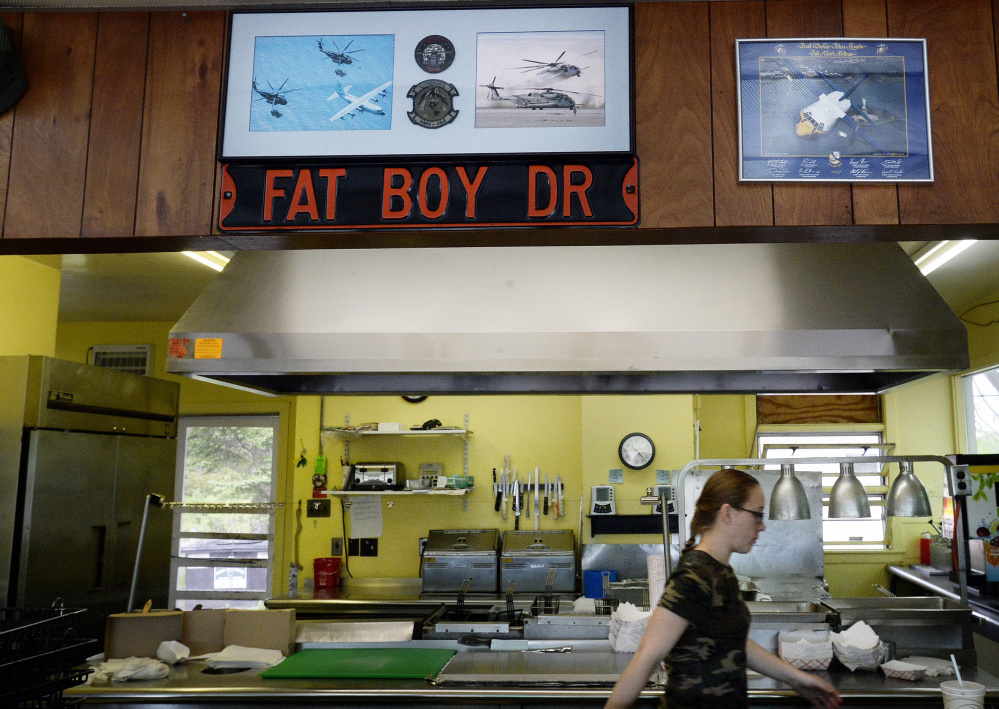 "Jay Spaltrow, a car hop at Fat Boy Drive-In in Brunswick, walks through the kitchen in 2016. The diner, which is now up for sale, opened in 1955 and has been serving up burgers, BLTs and popular onion rings since. Its owners said after more than 30 years of work, they're ""all burnt out."" The photos above Spaltrow are an homage to the Brunswick Naval Air Station."