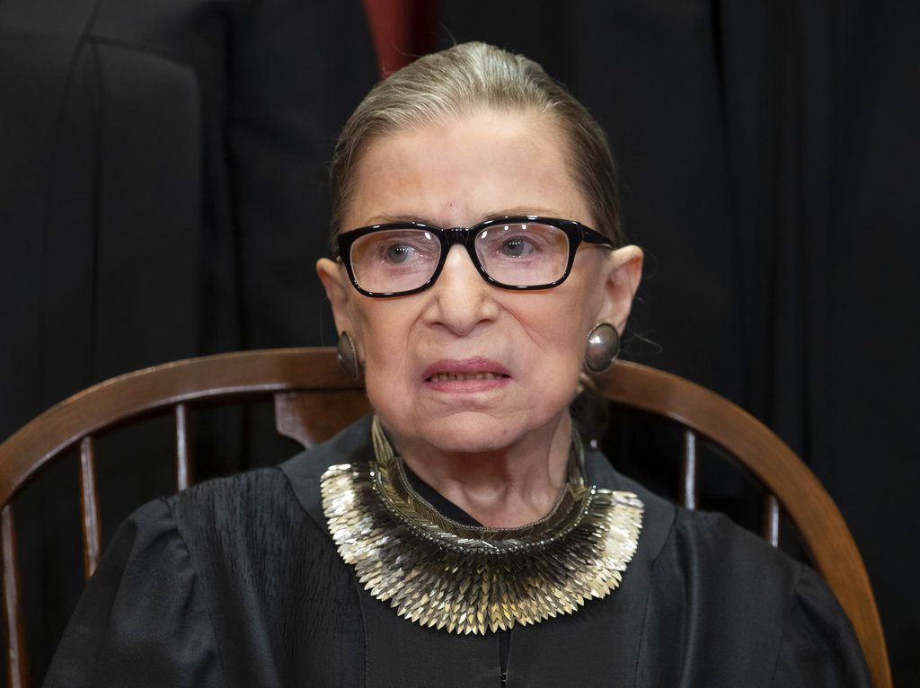 Associate Justice Ruth Bader Ginsburg sits with fellow Supreme Court justices for a group portrait at the Supreme Court Building in Washington, Friday, November 30. The Supreme Court says Justice Ruth Bader Ginsburg has undergone surgery to remove two malignant growths from her left lung. It is Ginsburg's third bout with cancer since joining the court in 1993.