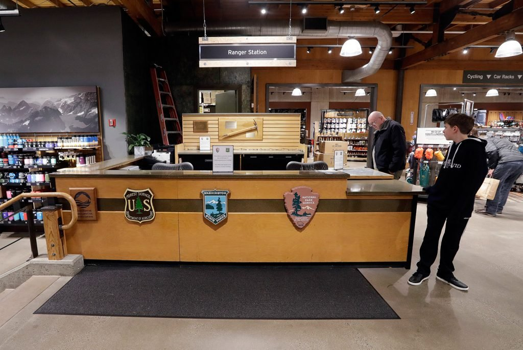 REI Co-op customers in the company's Seattle store stand near a ranger station kiosk that was closed Wednesday because of the federal government shutdown. The desk is normally staffed by rangers who provide information and passes for public lands in Washington state.