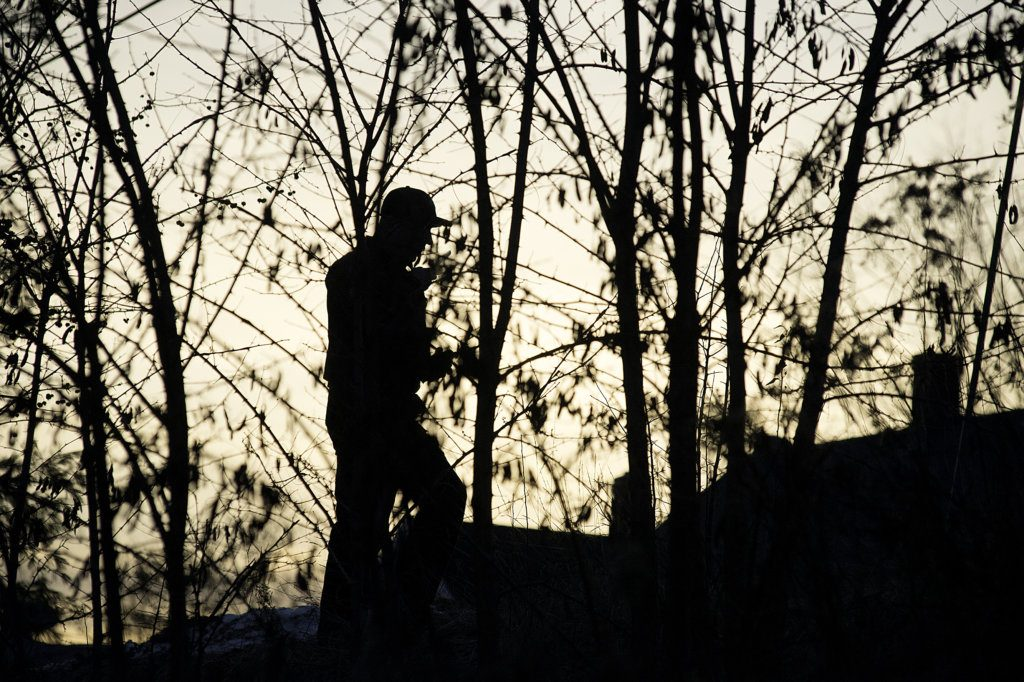 A Lewiston police officer climbs up an embankment along Olive Avenue while searching for an armed and despondent man on Thursday evening.