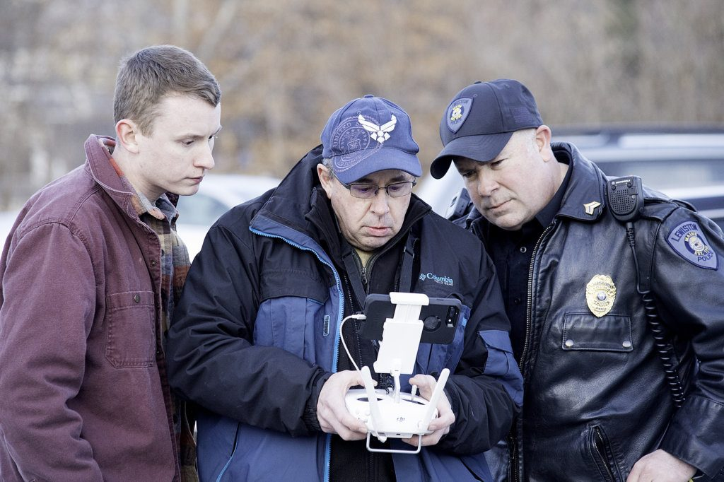 Robert Ullrich, right, of the Lewiston Police Department looks over the shoulder of Sun Journal photographer Russ Dillingham as Dillingham uses his drone to help search the woods for a 59-year-old man who was found dead from a self-inflicted gunshot. Dillingham's son, Ryan, is at left.