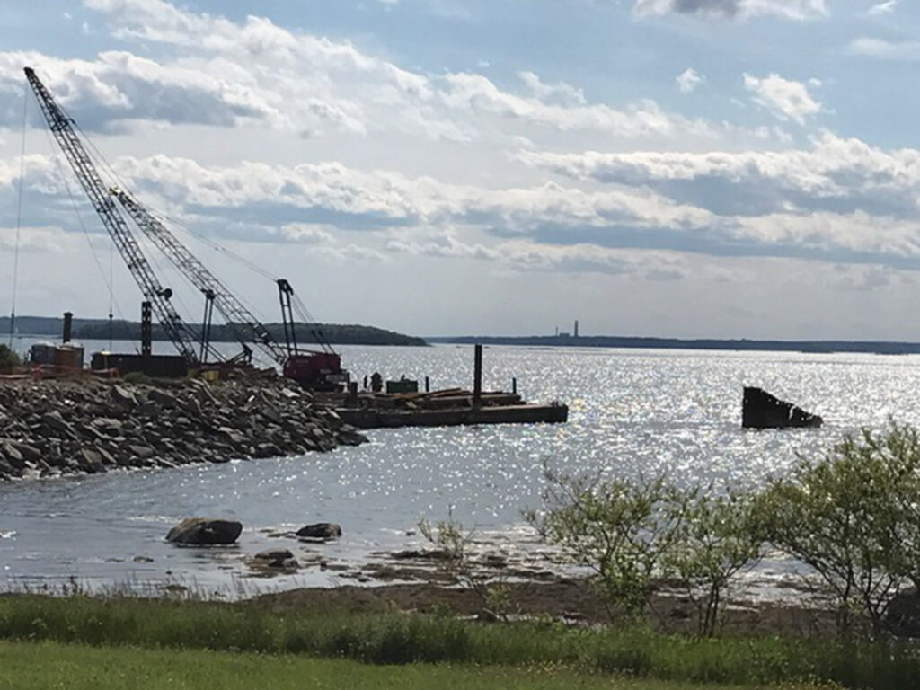 Workers from Reed & Reed remove the old pier off Mitchell Field in June.