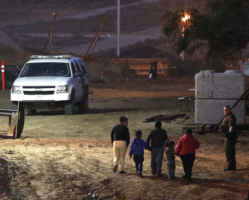 Migrants traveling with children walk up a hill to a waiting U.S. border patrol guard just inside San Ysidro, California, after climbing over the border wall from Playas de Tijuana, Mexico on Monday.