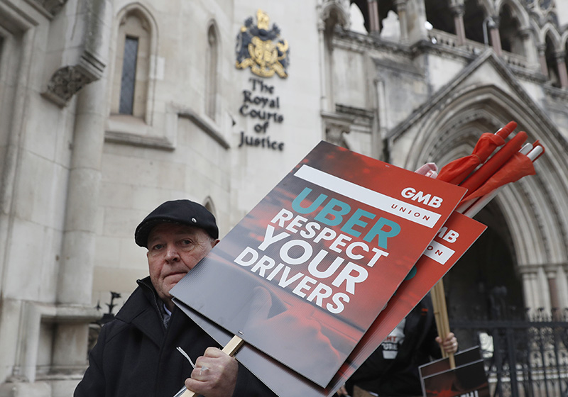 A member of the GMB union holds onto placards as he takes part in a GIG economy workers protest outside the Royal Courts of Justice ahead of a legal hearing over employment rights in London in October.