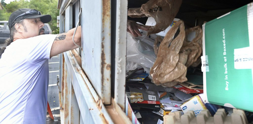 Stephen Mingo recycles items in a city bin Sept. 6 behind the Buker Center in Augusta.