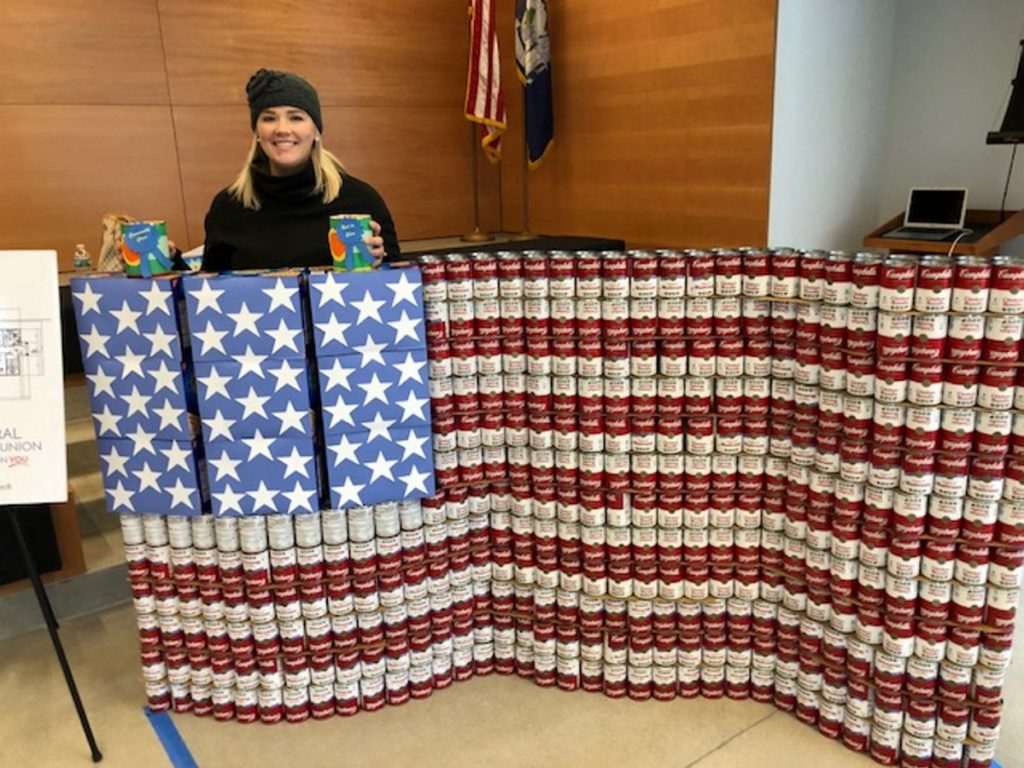 Alexandra Fabian, marketing and business development specialist for KV Federal Credit Union, stands on Saturday behind an American Flag sculpture made of Campbell's soup cans and Honey Maid graham cracker boxes. The entry won Best in Show and Community Choice awards during a statewide Day of Service event in the Chace Community Forum in downtown Waterville.