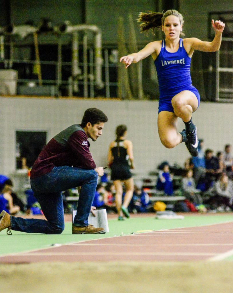 Kennebec Journal photo by Joe Phelan   Lawrence's Payton Goodwin flies during the triple jump Saturday at Bowdoin College in Brunswick.