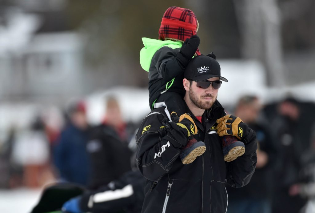 Courtney Ellis walks around the snowmobiles on display with his sone Saul atop his shoulders at the Snodeo in Rangeley on Friday, Jan. 21, 2017.