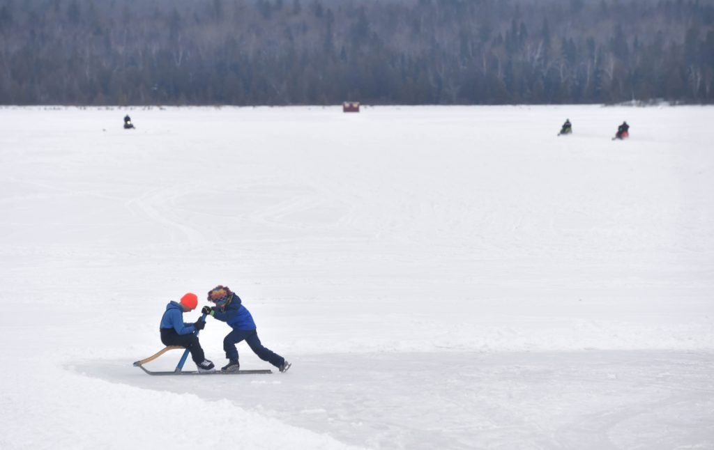 Eamon Mather, 5, pushes his friend Ryan Wing, 10, around the ice at the Snodeo in Rangeley on Friday, Jan. 21, 2017.