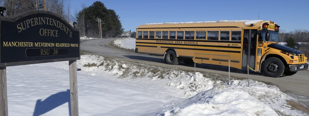 A bus exits Millard Harrison Drive, the access road to Maranacook Community High School. Maranacook Community Middle School and the superintendent's office, on Monday in Readfield. Regional School Unit 38's voters have approved a plan to repave the road, among several facility projects.