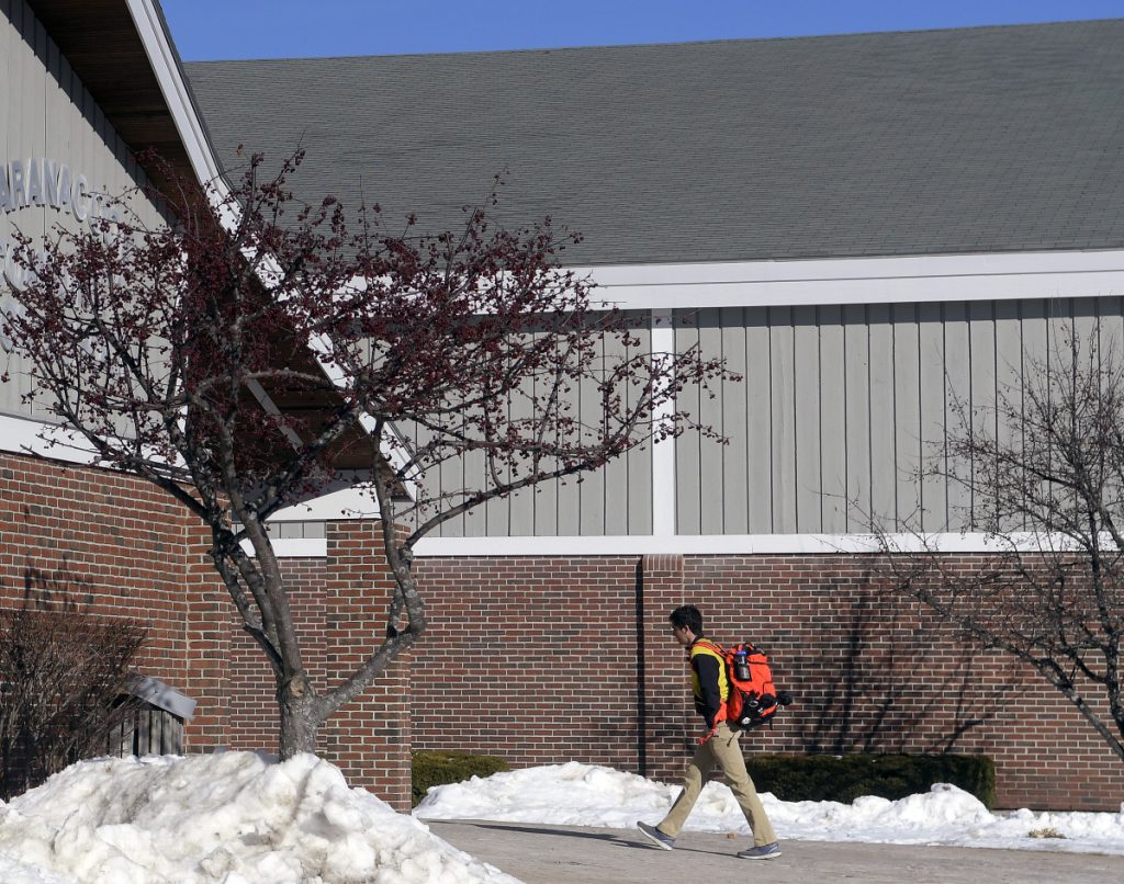 A student enters Maranacook Community High School on Monday in Readfield. Regional School Unit 38 voters have approved a bond to put a new roof on the school, among several facility projects.