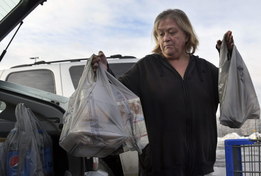 Earlinda Nirza, of Augusta, collects plastic bags full of groceries after shopping at Walmart in Augusta on Thursday. City councilors in Augusta discussed a proposal to ban plastic bags Thursday.