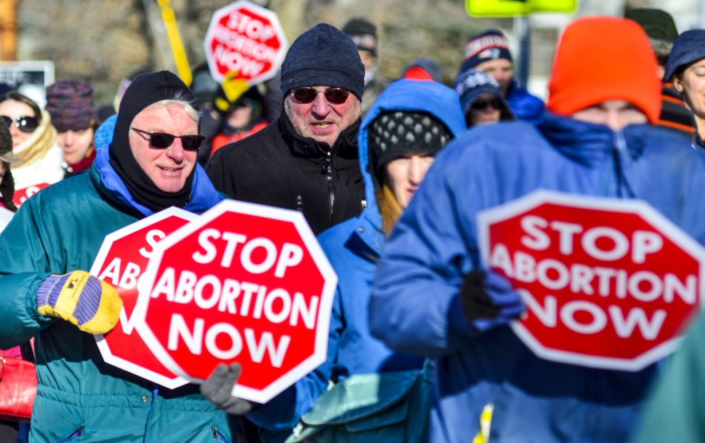 Anti-abortion rally participants walk from the St. Michael School gymnasium toward the Maine State House on Saturday in Augusta.