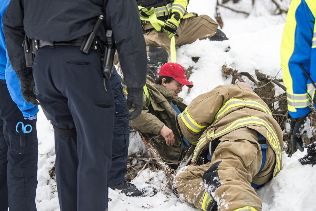 Waterville fire-rescue technician Glen Bordas lies on the ground as he and other rescue workers from Delta Ambulance and the Waterville police and fire departments pull Dias Greene, 15, to safety Jan. 5 after he fell into a hole in the woods south of the Hathaway Creative Center in Waterville.
