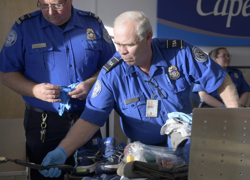 Transportation Security Administration screeners examine luggage Monday at the Augusta State Airport. The federal employees are deemed essential, but they have been working without pay since Dec. 22, when the federal government was shut down.