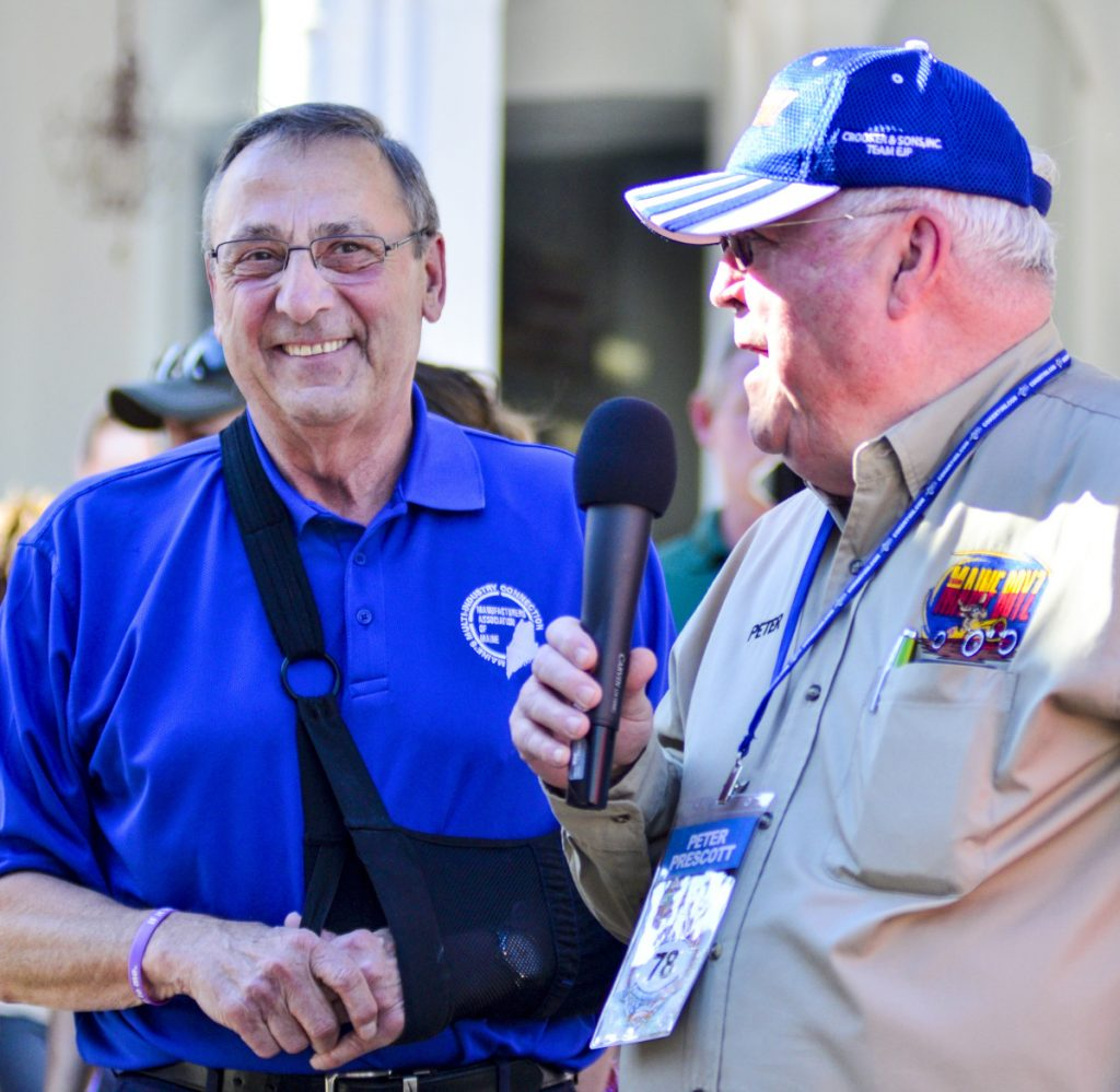 Gov. Paul LePage, left, smiles as Peter Prescott, who was the first to drive through the Great Race Arch, speaks to the crowd on Water Street on June 26 in Gardiner.