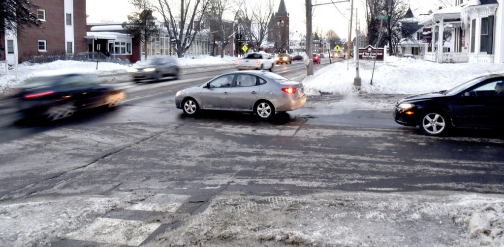 Traffic passes at the busy intersection and crosswalk at Main and South streets in Farmington near the University of Maine campus properties on Monday.